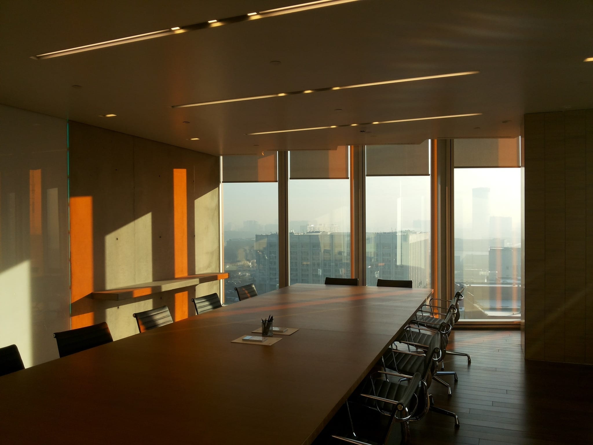 Large office board room with table and chairs beside large floor length windows to increase natural light